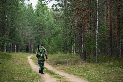 Man Walking In Hunting Boots Through Forest.