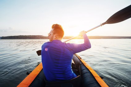 Man in inflatable kayak on a lake with fantastic sunset